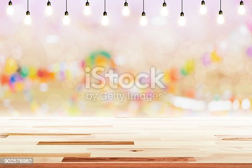 841276202 istock photo Empty wooden table with light bulb in night party background blurred. 902578982