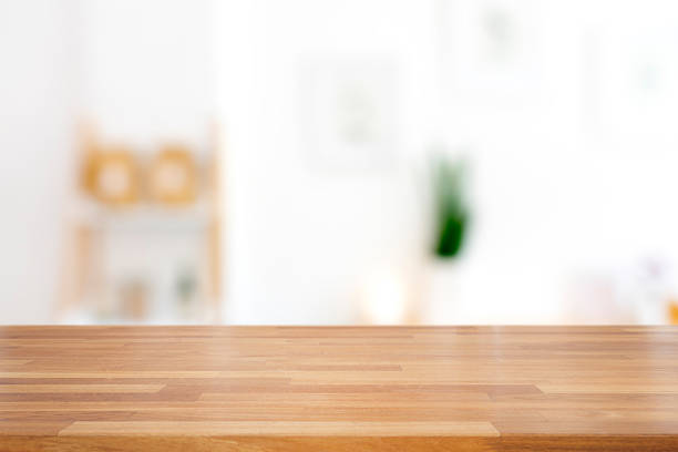 Empty wooden table with living room background Empty wooden table with living room background , Ready for product montage empty desk stock pictures, royalty-free photos & images