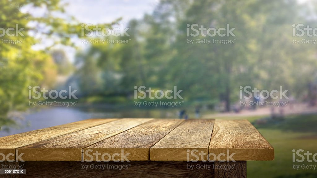 Empty wooden table with out of focus outdoor background stock photo