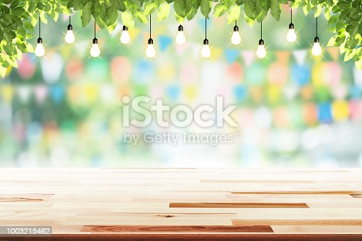 istock Empty wooden table with party in garden background blurred. 1003215462