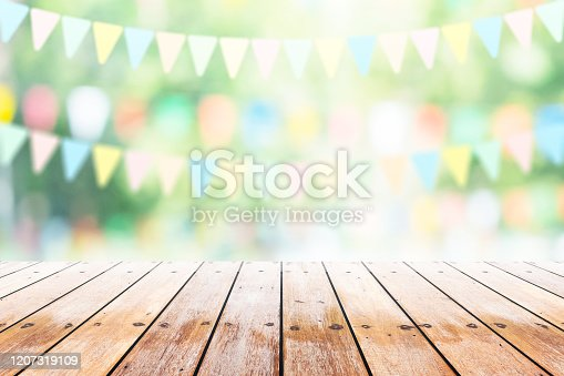 istock Empty wooden table with party in garden background blurred. 1207319109