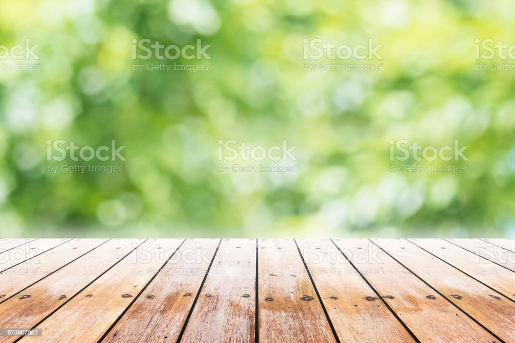 Empty wooden table with party in garden background blurred. Empty wooden table with party in garden background blurred. Archival Stock Photo