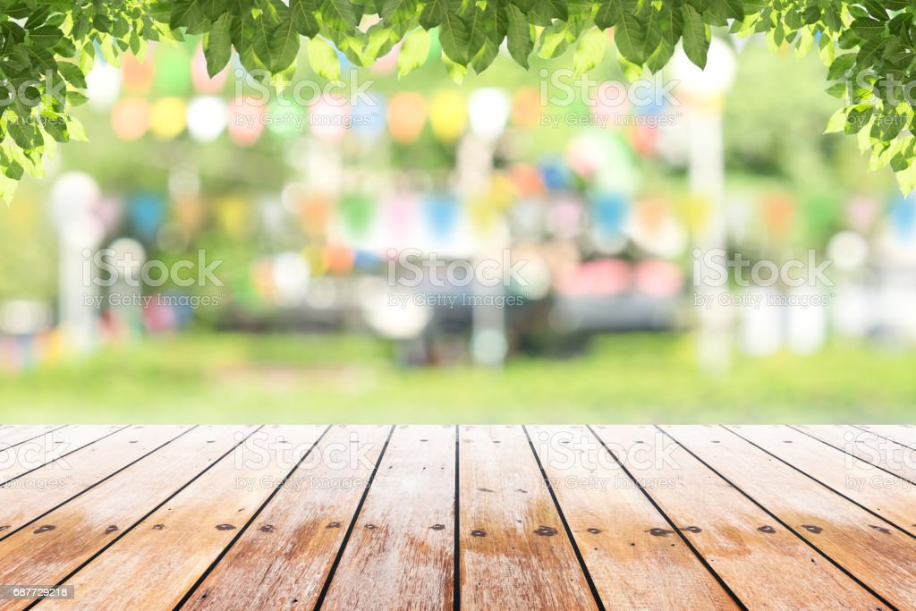 Empty wooden table with party in garden background blurred. - Photo