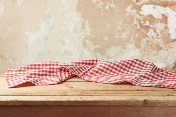 Empty wooden table with red checked tablecloth over rustic wall background. stock photo
