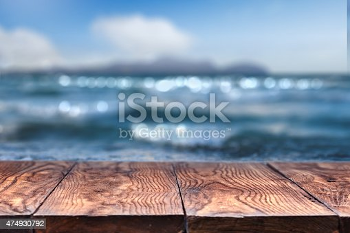 istock Empty wooden table with sea on background 474930792