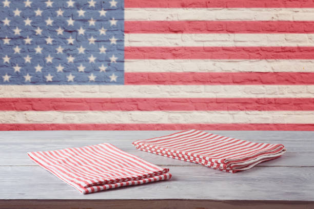 Empty wooden table with striped tablecloth over brick wall with american flag. 4th of july USA independence day mock up for design. stock photo