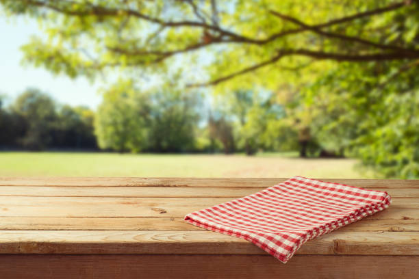 empty wooden table with tablecloth over autumn nature park background - picnic foto e immagini stock