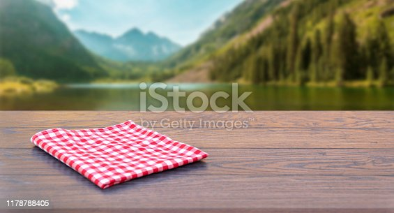 989111446istockphoto Empty wooden table with tablecloth over autumn nature park background 1178788405