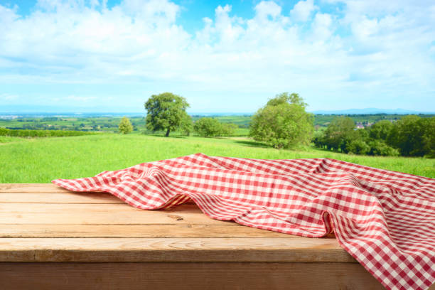 Empty wooden table with tablecloth over summer meadow background stock photo