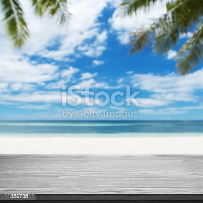 677933036 istock photo Empty wooden table with tropical beach background 1135673511