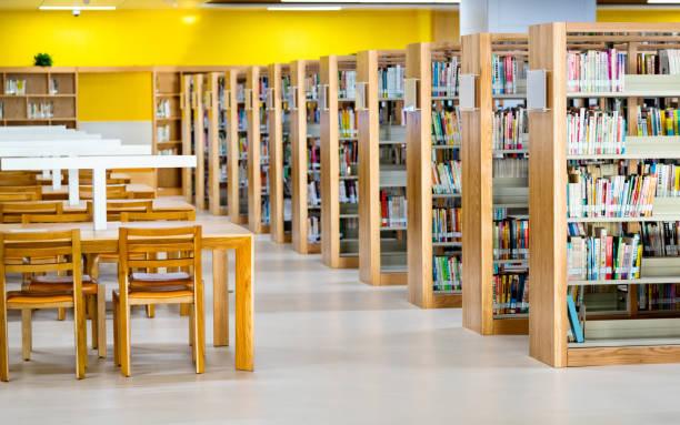 mesas de madera vacías en la biblioteca pública - biblioteca fotografías e imágenes de stock