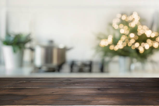 empty wooden tabletop for display products and blurred kitchen with christmas tree as background. - christmas table foto e immagini stock