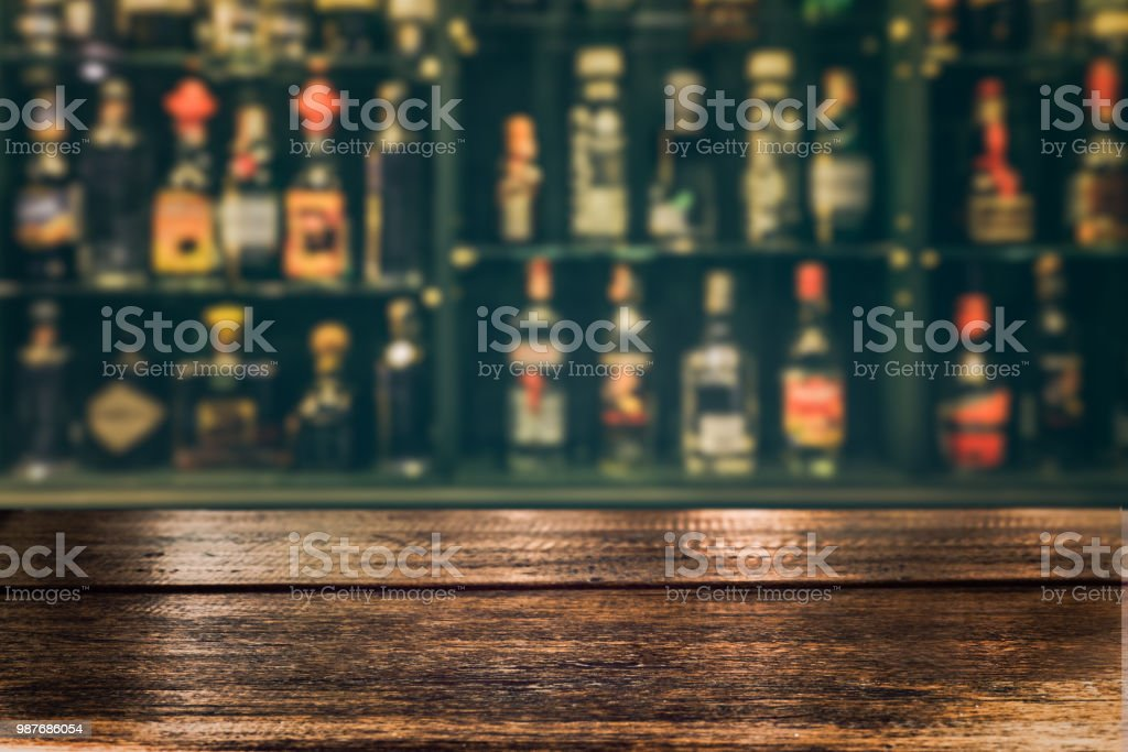 Empty wooden tabletop with blurred counter bar and bottles background...