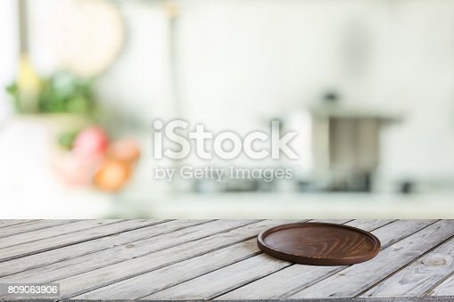 istock Empty wooden tabletop with cutting board and defocused modern kitchen for display or montage your products. 809063906