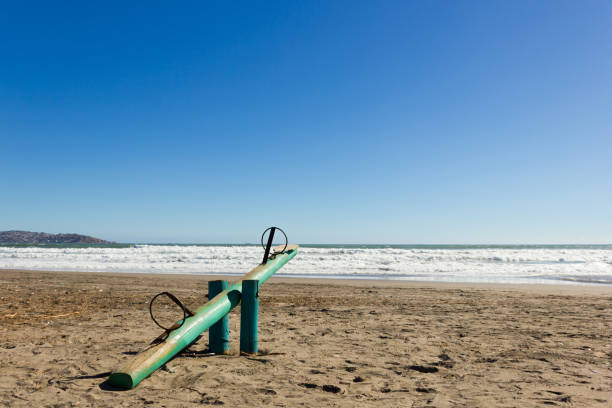 Empty wooden teeter totter on sunny day in La Serena beach, Chile stock photo