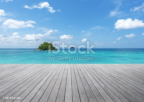 Empty wooden terrace and tropical ocean with clear sky background