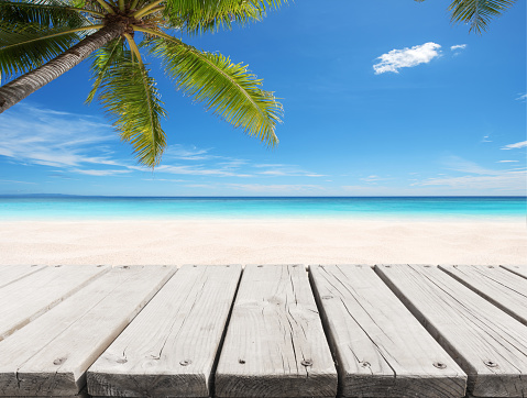 Empty wooden terrace with tropical beach and clear sky background
