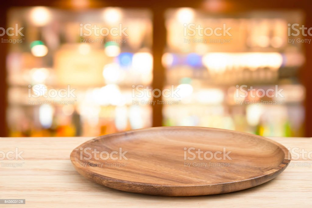 Empty wooden tray on perspective wooden table on top over blur wine bar in cafe background. Can be used mock up for montage products display or design layout. stock photo