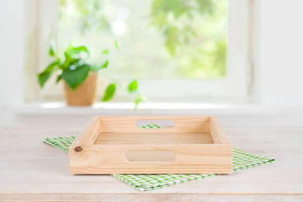 Empty wooden tray on table over blurred summer window background stock photo