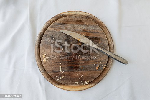 Empty wooden tray with cutlery and bread crumb on table