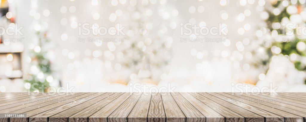 Leere woooden Tischplatte mit abstrakten warmen Wohnzimmer Dekor mit Weihnachtsbaum String Licht Unschärfe Hintergrund mit Schnee, Urlaub Hintergrund, Mock up Banner für die Anzeige von Werbeprodukt. - Lizenzfrei Abstrakt Stock-Foto