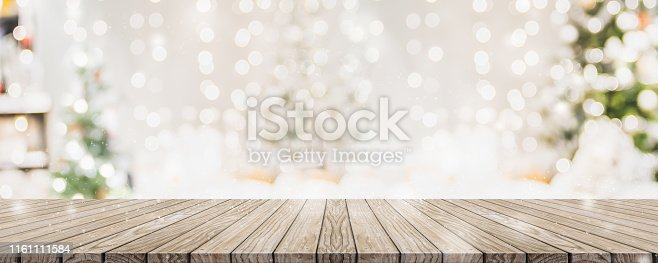 istock Empty woooden table top with abstract warm living room decor with christmas tree string light blur background with snow,Holiday backdrop,Mock up banner for display of advertise product. 1161111584