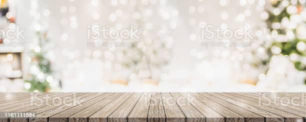 Leere Woooden Tischplatte Mit Abstrakten Warmen Wohnzimmer Dekor Mit Weihnachtsbaum String Licht Unschärfe Hintergrund Mit Schnee Urlaub Hintergrund Mock Up Banner Für Die Anzeige Von Werbeprodukt Stockfoto und mehr Bilder von Abstrakt