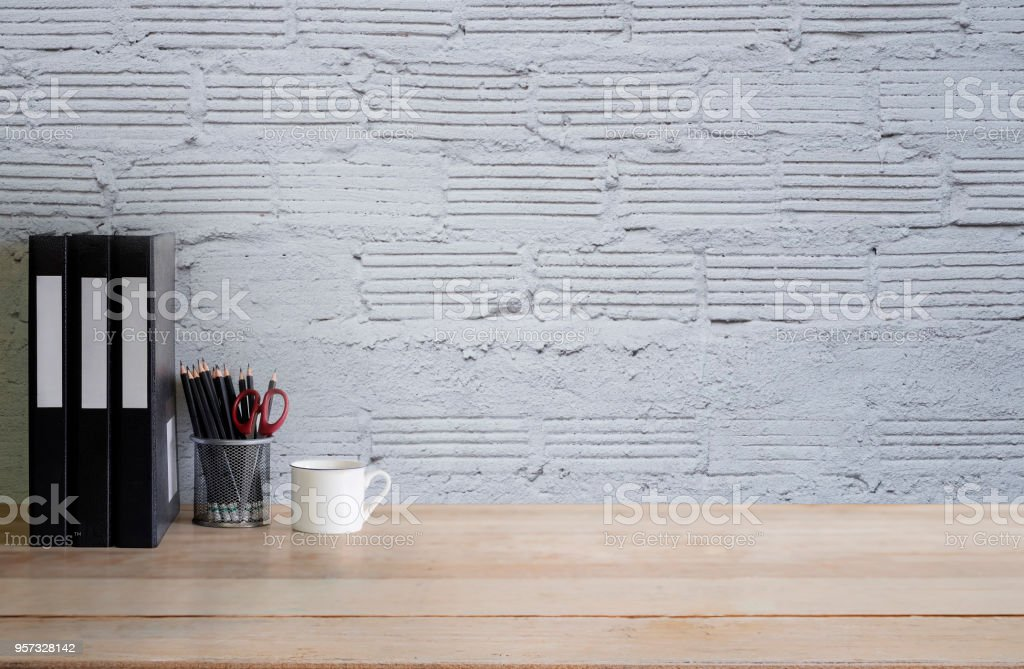 Empty work desk office with mug, pencil and file document a wood table and white brick wall. stock photo
