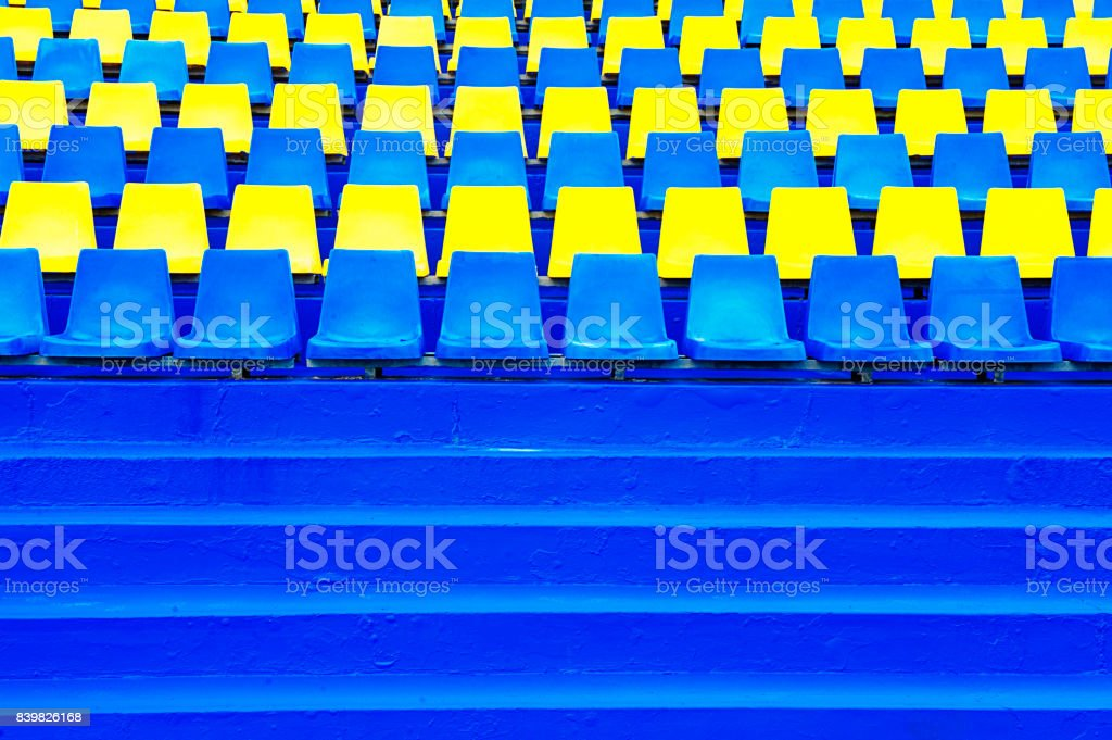 Empty yellow and blue bleacher seats at a staduim stock photo