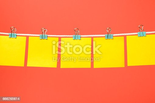 istock Empty yellow paper notes on the string over color background 666265614