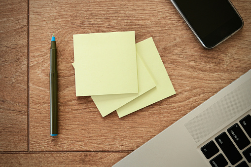 Empty yellow sticky note pads with pen, mobile, laptop