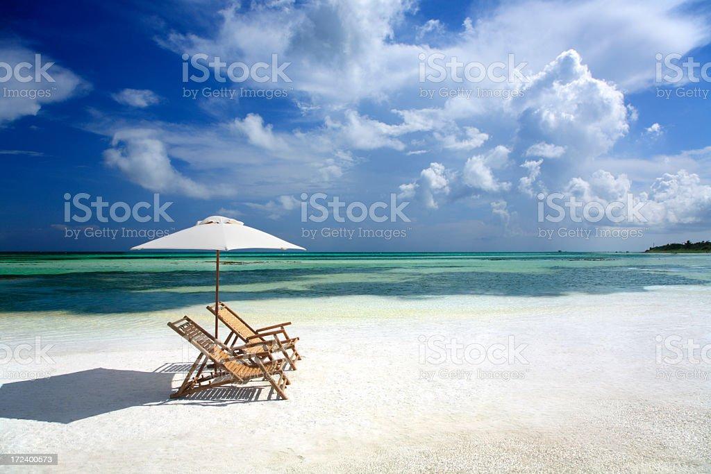 empy bamboo chairs and umbrella on a sandbar in Florida royalty-free stock photo