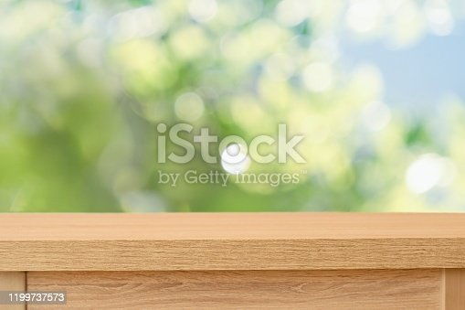 639809128 istock photo Emtpy tabletop with green fresh spring blurred background 1199737573