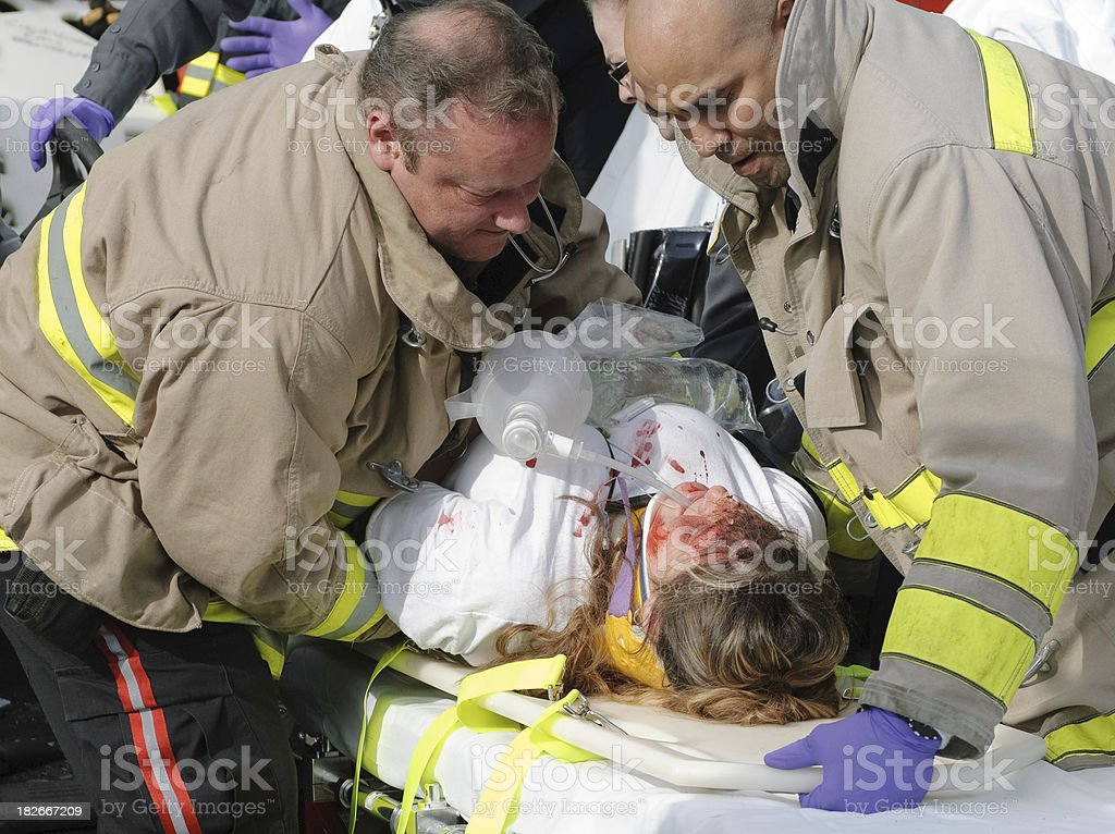 EMTs Lower Patient Onto A Stretcher royalty-free stock photo