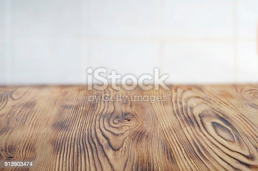 istock Emty clear aged brown wooden table for product placement . Kithen rustic rural  table for food. White cblurred cell tile on the backgroud 913903474