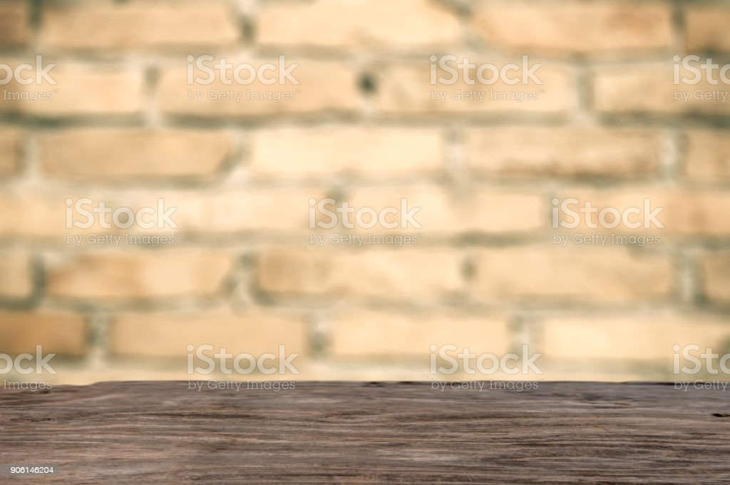 Emty wooden table in front of brick wall stock photo