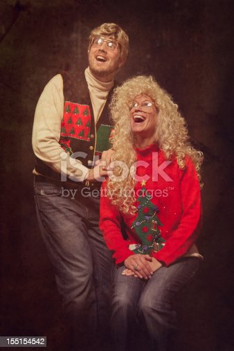 A man and woman from the 1980s with glasses, highlighted hair, and classy Christmas sweaters poses for a picture at a classic photo studio.  Intentional 80's style kitsch post processing emulation.  Vertical.