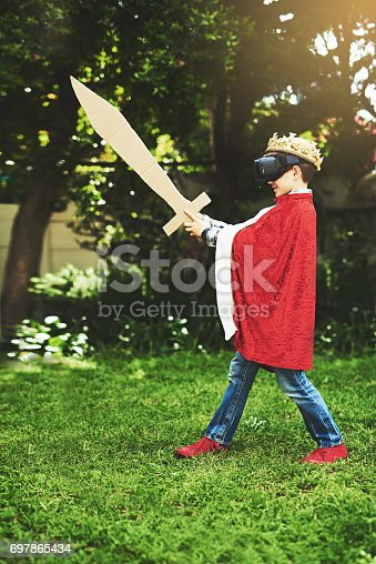 Shot of a little boy in a king's costume playing with a vr headset on