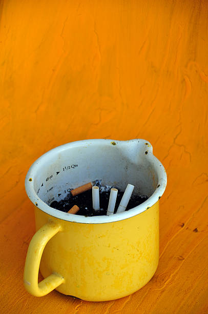 enamel cup with cigarette butt stock photo