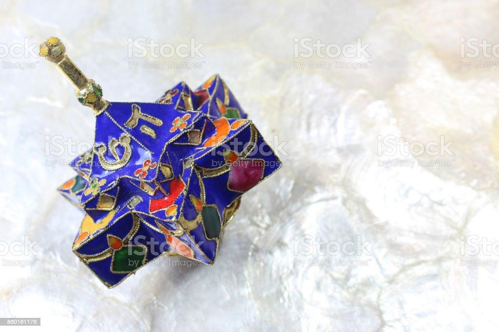 Enameled blue star shaped Hanukkah dreidel on a soft white background stock photo