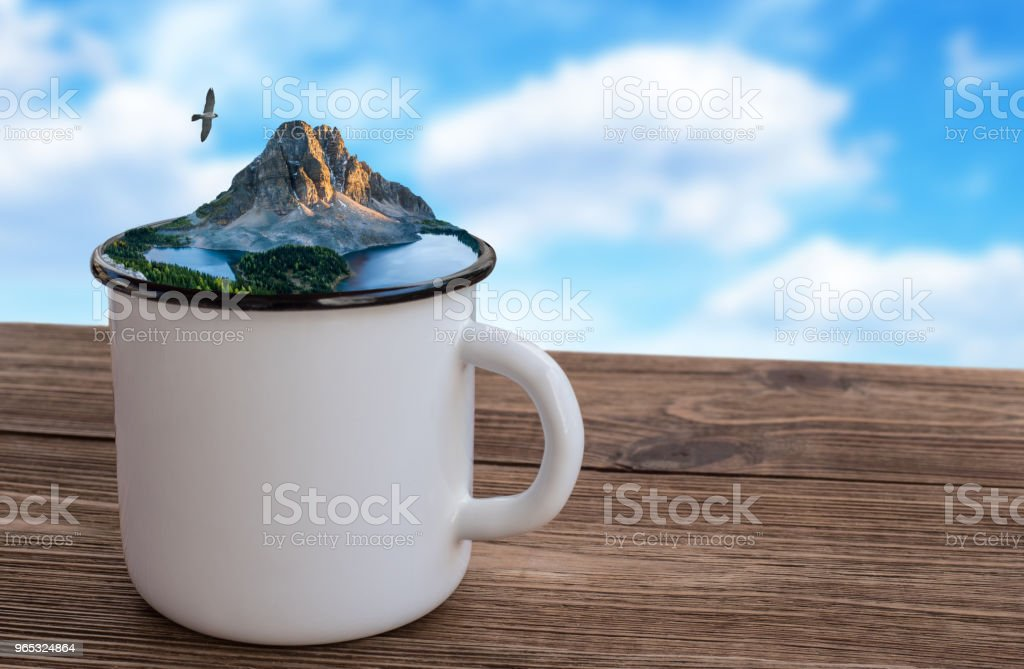 Enameled tourist mug with nature on the wooden table . royalty-free stock photo