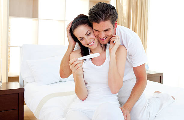 enamored couple finding out results of a pregnancy test - family planning stock photos and pictures