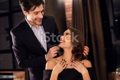 Gift of love. Enamored man giving beautiful necklace to his girlfriend in cafe, empty space