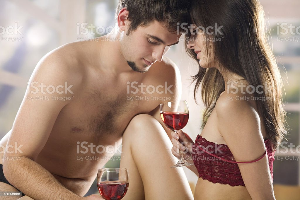 Enamoured couple drinking red wine on the bed in bedroom stock photo