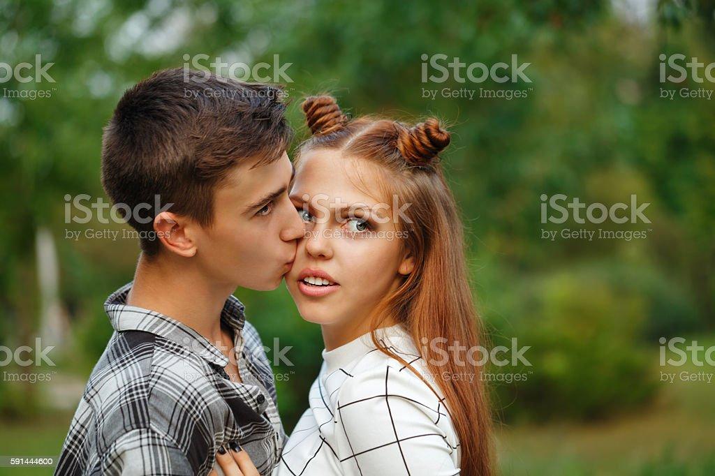 Enamoured kiss teens. stock photo