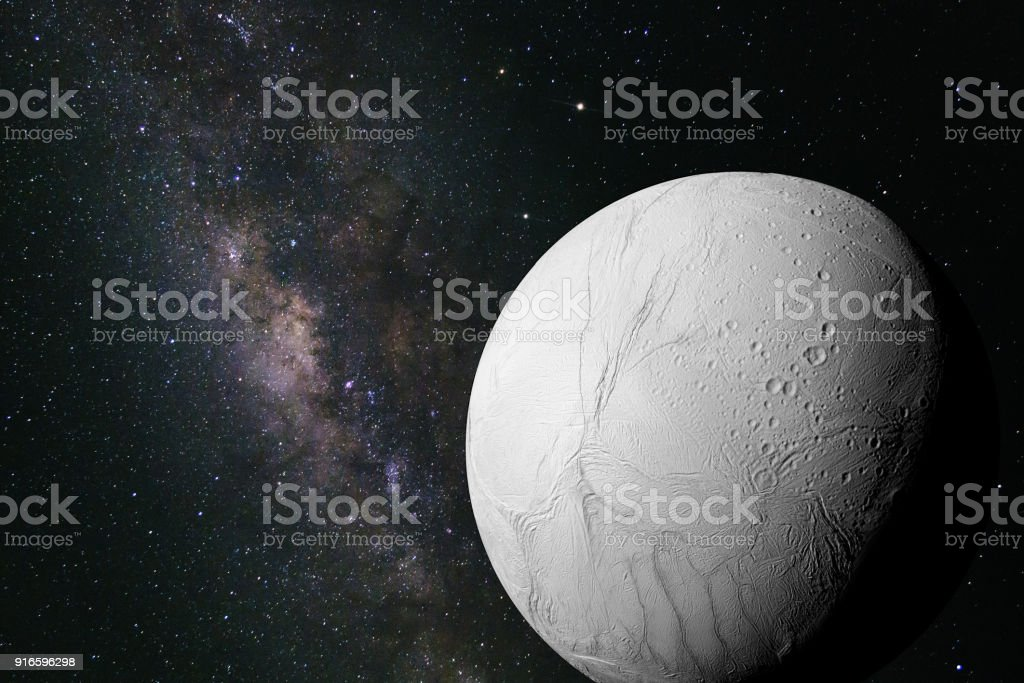 Enceladus, moon of the planet Saturn in front of the galaxy stock photo