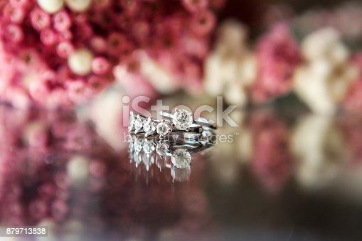 155315629istockphoto Enchanting diamond rings on flowered background 879713838