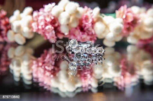 155315629istockphoto Enchanting diamond rings on flowered background 879713840