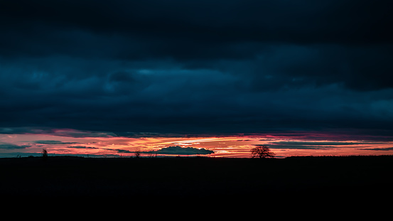 Enchanting sunrise with dramatic stormy cloudy sky before a thunderstorm storm, silhouette of a tree in a field at dawn on the horizon against the background of the rising sun in the early morning