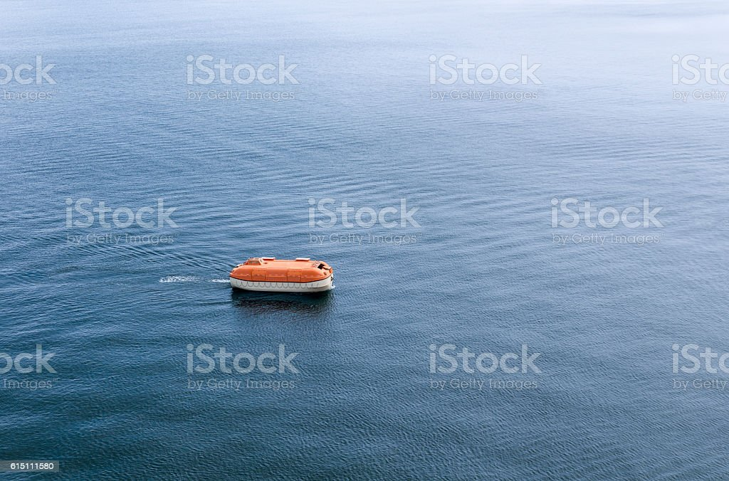 Enclosed rigid lifeboat awaiting rescue on sea expanse stock photo